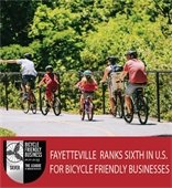 An image of a family riding bikes. Text: Fayetteville ranks 6th in U.S. for bicycle friendly businesses.