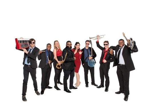 Image of the eight members of Jukeboxx, dressed in black and red and holding their instruments