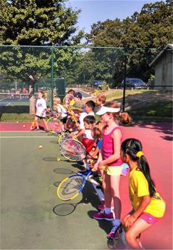Tennis campers line up on court and practice their stances