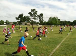 Campers practice dribbling soccer balls down soccer field while being supervised