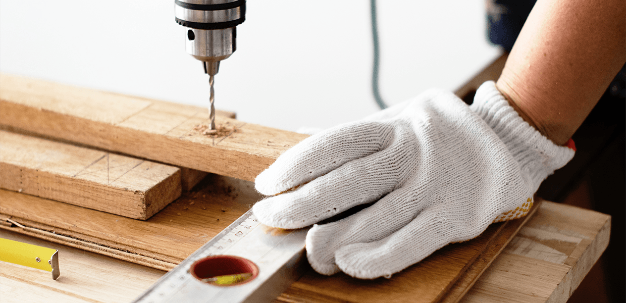 A pair of gloved hands drives a screw into a board with a powerdrill