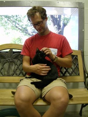 Man in red shirt sits on a bench and pets a black cat