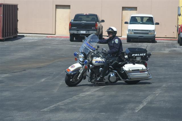 Policeman on Motorcycle in Parking Lot