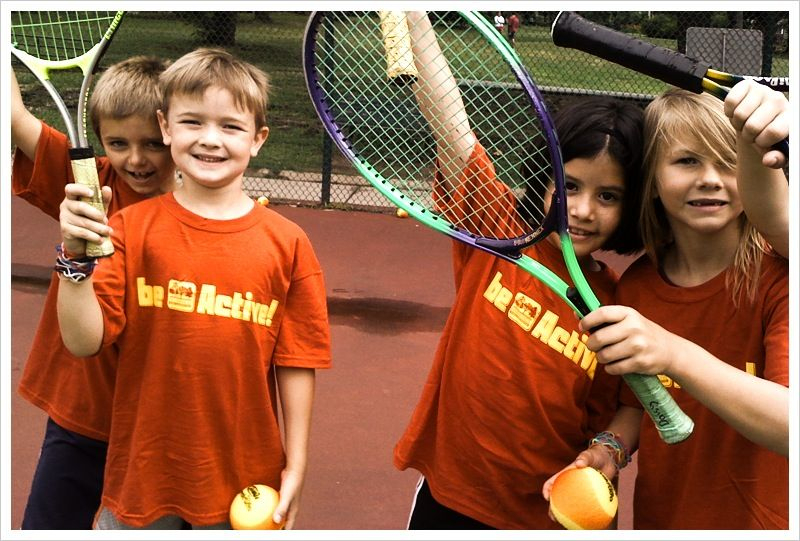 Children hold up tennis racquets and smile for the camera
