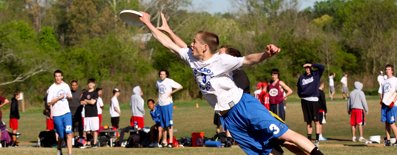 A boy dives to grasp frisbee during an ultimate disc game