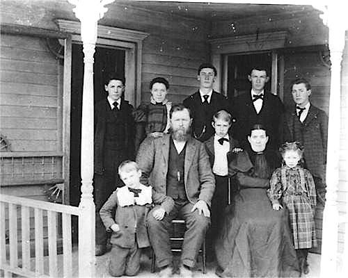 A black and white 19th century photograph of a family of ten gathered on a wooden front porch