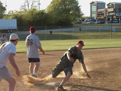 Man runs around base during a softball game at Lake Fayetteville