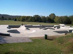 Skate park area surrounded by green lawns and trees in the distance